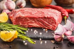 Raw whole piece of beef on slate with spices, fresh raw meat. Raw whole piece of beef on slate with spices, dark background, copy space Stock Images