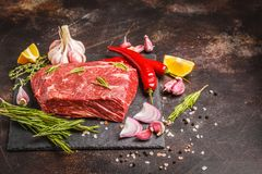 Raw whole piece of beef on slate with spices, fresh raw meat. Raw whole piece of beef on slate with spices, dark background, copy space Stock Image