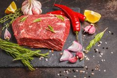 Raw whole piece of beef on slate with spices, top view. Raw whole piece of beef on slate with spices, dark background, copy space Royalty Free Stock Images