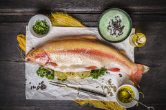 Raw whole  rainbow trout on dark wooden table with herb and lemon,preparation Stock Photography