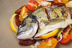 Raw whole sea bream fish and vegetables ingredients Royalty Free Stock Photos