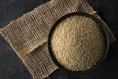 Raw, whole, unprocessed quinoa seed in bowl on wood board Royalty Free Stock Photo