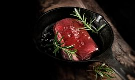 Raw Wild Boar Fillet. Uncooked, raw fillet of wild boar, prepared for frying in a black wrought iron skillet with extra virgin olive oil, rock salt and rosemary stock photography