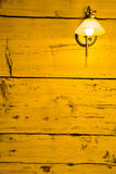 Raw wooden wall with retro lamp. Lemon color. Royalty Free Stock Photography
