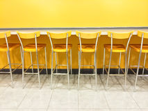 Raw of yellow chairs in a cafeteria Stock Images