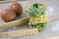 Raw yellow and green pasta with two eggs on wooden table Stock Photos