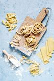 Raw yellow italian pasta pappardelle, fettuccine or tagliatelle on a blue background, close up. stock photo