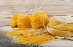 Raw yellow italian pasta pappardelle, fettuccine or tagliatelle stock images