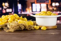 Raw yellow pasta conchiglie with restaurant. Lot of whole raw yellow pasta conchiglie variety on jute cloth in a ceramic stewpan with restaurant in background royalty free stock images