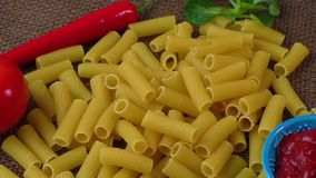 Raw yellow pasta, macaroni on  sack background stock video footage