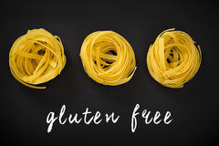 Raw yellow pasta with text written on chalkboard. Gluten Free. Raw yellow tagliatelle pasta with hand lettering text written on a chalkboard. Gluten Free Stock Photography
