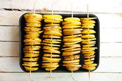 Raw yellow potatoes in a peel, cut into slices. Pieces are strung on wooden skewers, laid out horizontally in four rows Stock Photo