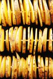 Raw yellow potatoes in a peel, cut into slices. Pieces are strung on wooden skewers, laid out in three rows. And prepared for further cooking Royalty Free Stock Photography