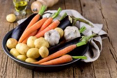 Raw Young Potatoes Carrot Garlic and Eggplant on Black Plate Variety of Raw Vegetables ready to Cook Fresh Natural Vegetables. Organic Healthy Food Olive Oil royalty free stock photography