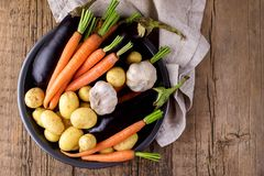 Raw Young Potatoes Carrot Garlic and Eggplant on Black Plate Variety of Raw Vegetables ready to Cook Fresh Natural Vegetables. Organic Healthy Food Olive Oil stock photos