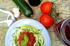 Raw zucchini noodles with tomato topping. A light and refreshing spring approach to pasta and sauce. This raw dish is packed with B vitamins, fiber, protein, and Royalty Free Stock Photos