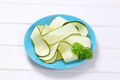 Raw zucchini strips. Plate of raw zucchini strips on white wooden background Stock Photography