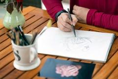 rawing在从照片的铅笔的妇女手 库存图片