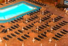 Raws des lits pliants devant la piscine dans une station de vacances, vue de nuit Vacati Photos stock