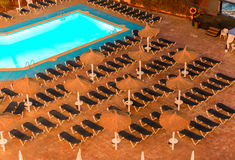 Raws of sunbeds in front of pool in a resort, night view. Vacati Stock Photos