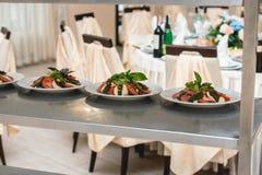 Raws van de salade van de tomatenmozarella in witte plaat met eigengemaakte chees en de ingrediënten op een metaal rekken stock fotografie