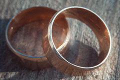 Rayé deux anneaux de mariage larges d'or sur la surface en pierre Image libre de droits