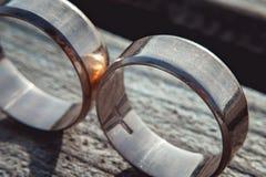 Rayé deux anneaux de mariage larges d'or sur la surface en pierre Images libres de droits