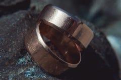 Rayé deux anneaux de mariage larges d'or sur la surface en pierre Images stock