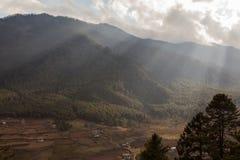 Ray av solljus till och med molnen i den Bumthang dalen, Bhutan arkivfoton
