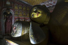 A ray of light hits a reclining Buddha statue in Cave Three at the Dambulla Cave Temples in Sri Lanka. Royalty Free Stock Photography