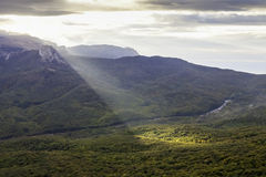 Ray of morning light over forest mountain slopes Stock Photo