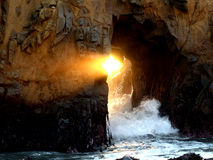A ray of sun light is seen from sea cave at Big Sur, CA Stock Image