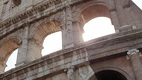 A ray of sun passes through the arches of the Colosseum in Rome, Italy.