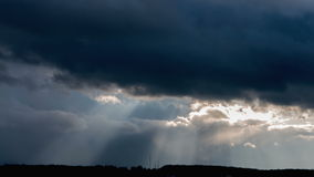 A ray of sunlight breaking through dark clouds stock video footage