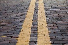Raya amarilla en la calle del ladrillo fotografía de archivo