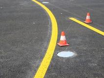 Rayas amarillas con el cono del tráfico Imagen de archivo