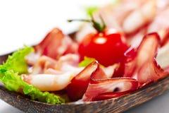 Rayas del tocino servidas con verdes y el tomate. En el fondo blanco Imagen de archivo libre de regalías