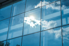 Rayo de Sun y reflexión del cielo azul en el edificio de oficinas de la ventana, Busin Foto de archivo libre de regalías