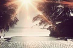 Rayon de soleil lumineux au-dessus d'une piscine de luxe d'infini Photographie stock libre de droits