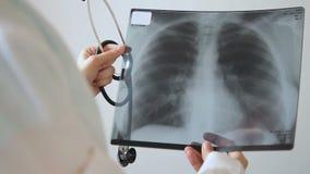 Rayon X qualifié de prises de docteur des poumons, se tenant dans la clinique à l'intérieur banque de vidéos