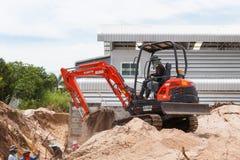 Rayong Tailândia - 9 de setembro de 2014: Trabalhador que conduz a máquina escavadora ao placin Imagem de Stock Royalty Free