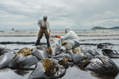 Workers remove and clean up crude oil spilled from Prao Bay Stock Images