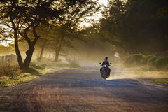 RAYONG THAILAND - NOV 8,2014 : villager riding motorcycle on bea. Utiful  dusty road ,motorcycle in most popular traveling vehicle in thailand rural Stock Photo