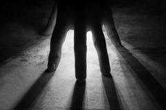 rayonne des rayons d'éclat de lumière par la silhouette de la main dans le noir images stock