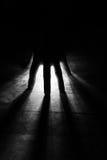 rayonne des rayons d'éclat de lumière par la silhouette de la main dans le noir photographie stock