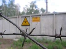 Rayonnement de signe sur la barrière grise du secteur restreint avec le barbelé photos stock