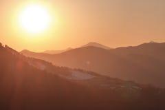 Rayons d'or du soleil au coucher du soleil dans les montagnes Photo stock