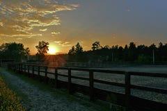 Rayons de coucher du soleil du soleil beau contre le ciel nuageux photographie stock libre de droits