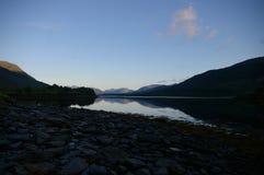 Rayons de lever de soleil de loch sur les montagnes Photo libre de droits