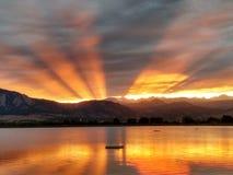Rayons de lumière crépusculaires rayonnant par derrière le coucher du soleil de lac de montagne Image stock